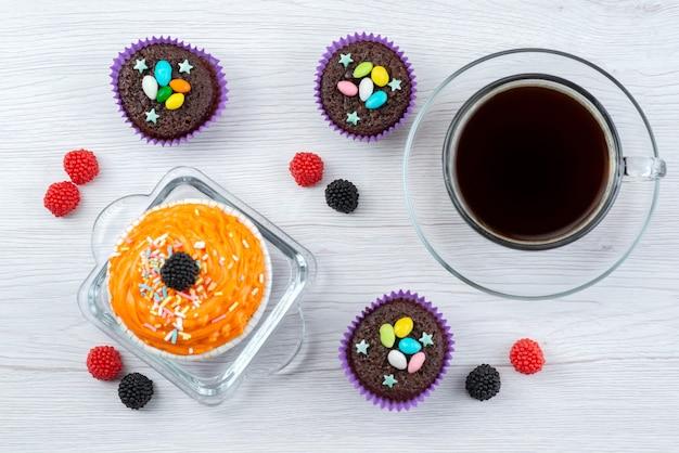 Eine draufsicht köstliche brownies innerhalb lila formen zusammen mit einer tasse tee auf weißen, bonbonfarbenen süßigkeiten