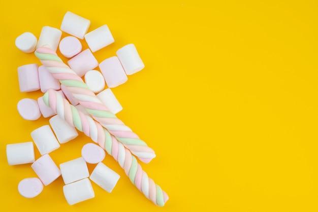 Eine draufsicht köstliche marshmallows auf gelben, zuckersüßen farbbonbons