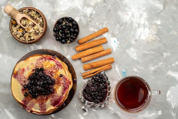 Eine draufsicht köstliche runde pfannkuchen lecker und rund gebildet mit blaubeertee und zimt gebildet