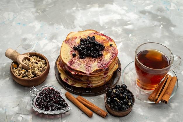 Eine draufsicht köstliche runde pfannkuchen lecker und rund gebildet mit blaubeertee und zimtpfannkuchengebäck