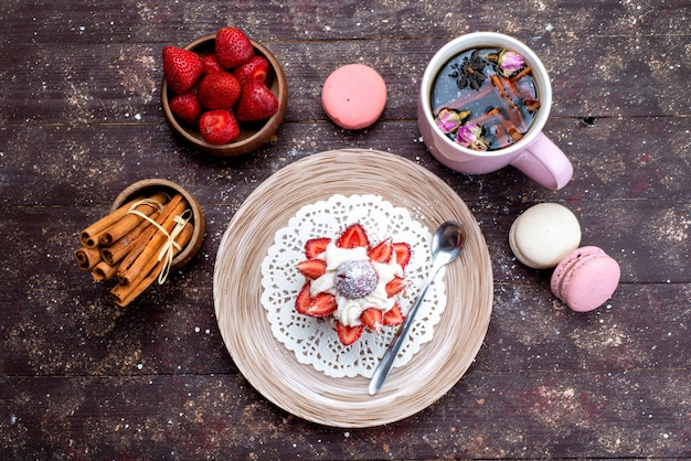 Eine draufsicht köstlicher kleiner kuchen mit sahne und frisch geschnittenen früchten zusammen mit zimt und macarons zusammen mit zimt auf dem braunen schreibtischobstkuchen