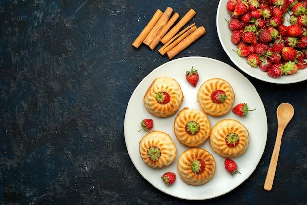 Eine draufsicht leckere kekse mit roten erdbeeren in weißer platte auf dem dunklen schreibtischkeks
