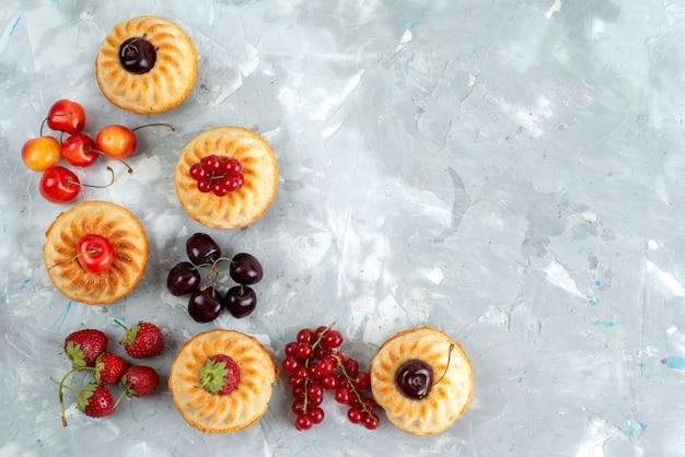Eine draufsicht leckere kuchen mit milden und saftigen roten früchten auf dem hellen schreibtischbeerenfruchtkuchen