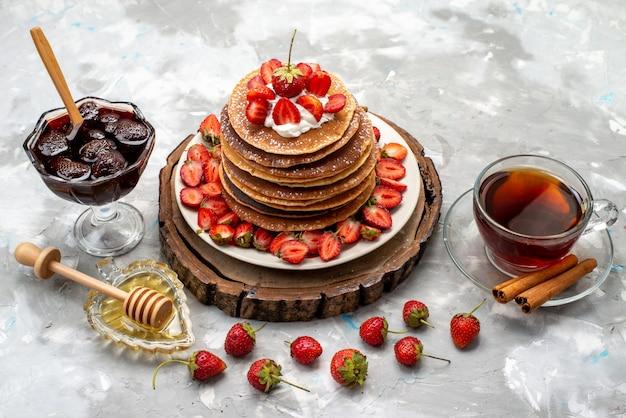 Eine draufsicht leckere runde pfannkuchen mit sahne-tee und erdbeeren auf dem hölzernen schreibtischkuchen