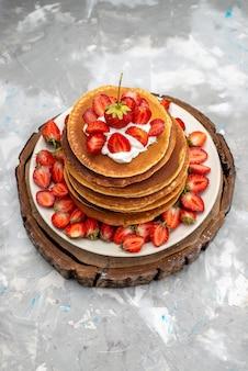 Eine draufsicht leckere runde pfannkuchen mit sahne und roten erdbeeren auf dem hölzernen hintergrundkuchen