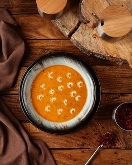 Eine draufsicht leckere suppe auf dem hölzernen schreibtischnahrungsmittelmahlzeitsuppenfoto