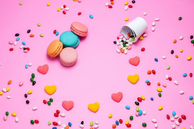 Eine draufsicht macarons und marmelade bunte französische kuchen zusammen mit mehrfarbigen bonbons auf dem rosa hintergrund süße süßigkeiten
