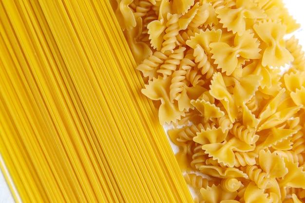Eine draufsicht rohe italienische nudeln, die wenig und lange auf dem hellen schreibtisch pasta italienisches essen mahlzeit gebildet
