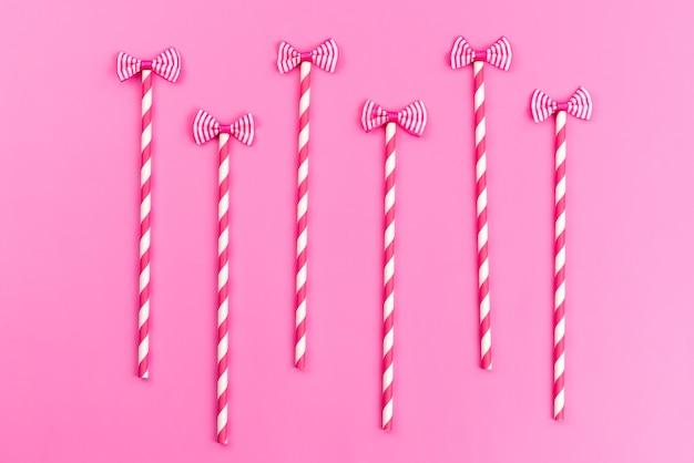 Eine draufsicht rosa-weiße stockbonbons mit niedlichen schleifen auf rosa, süßer zuckerfarbe