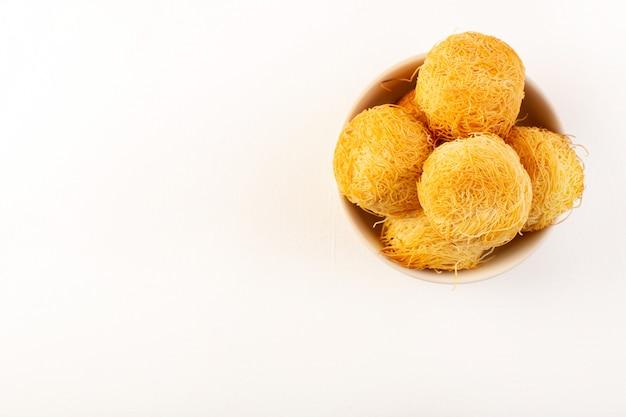 Eine draufsicht runde köstliche kuchen süße leckere runde gebackene backen innerhalb der weißen platte lokalisiert auf dem weißen hintergrund süße zuckerwaren