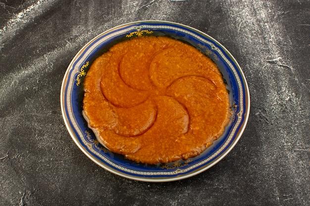 Eine draufsicht süßes köstliches halva leckeres östliches essen innerhalb platte auf der dunklen oberfläche