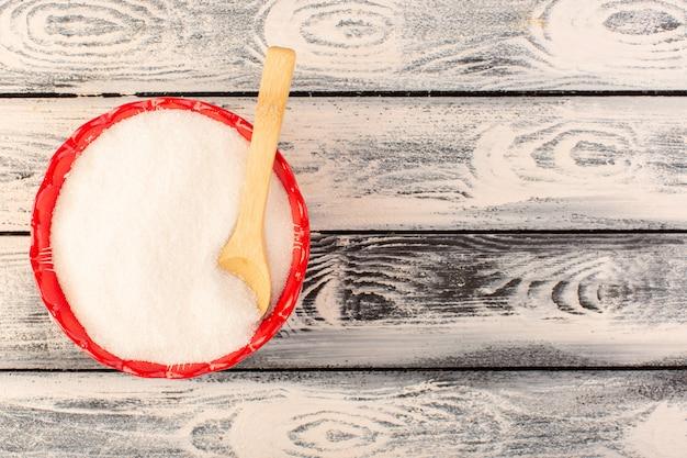 Eine draufsicht viel salz innerhalb der roten runden platte mit holzlöffel auf der grauen schreibtischsalzgewürzplatte farbe