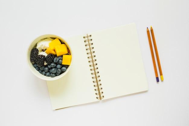 Eine draufsicht von bleistiften und von leerem gewundenem notizbuch mit gesunden früchten in der schale