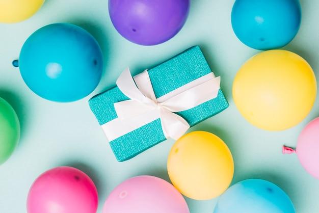 Eine draufsicht von bunten ballonen um die geschenkbox auf blauem hintergrund