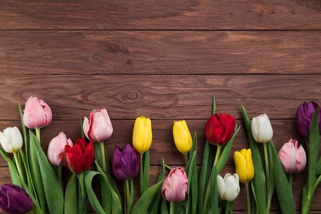 Eine draufsicht von bunten tulpen auf hölzernen betriebsoberflächenhintergrund