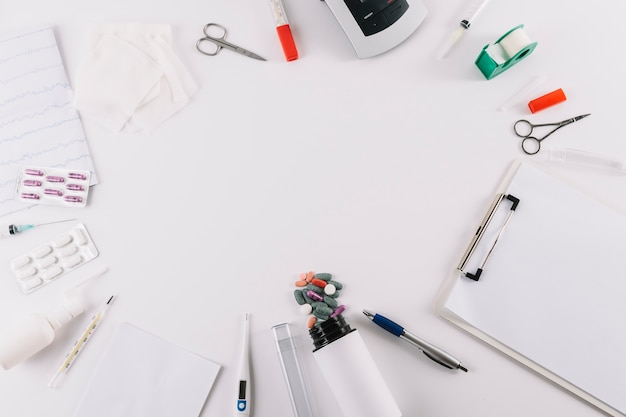 Eine draufsicht von medizinischen ausrüstungen und von pillen lokalisiert auf weißem hintergrund