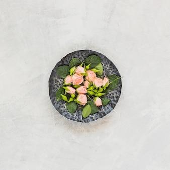 Eine Draufsicht von rosa Blumen auf Steinschale gegen konkreten Hintergrund