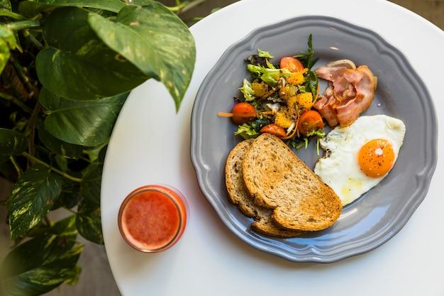 Eine draufsicht von smoothie und frühstück auf keramischer platte über der weißen tabelle nahe der epipremnum aureum anlage