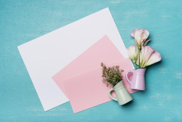Eine draufsicht von zwei blumenvasen mit leerem rosa und weißem papier auf strukturiertem hintergrund