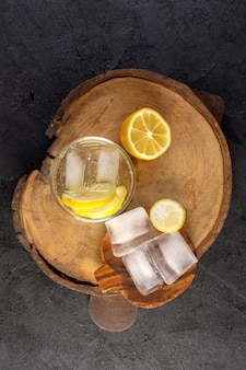 Eine draufsicht wasser mit zitrone frisch kühles getränk in glas mit eiswürfeln mit geschnittenen zitronen auf dem dunklen hintergrund cocktail trinken obst