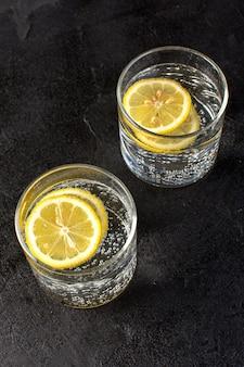 Eine draufsicht wasser mit zitrone frisch kühles getränk mit geschnittenen zitronen in transparenten gläsern auf dem dunklen hintergrund cocktail getränk frucht