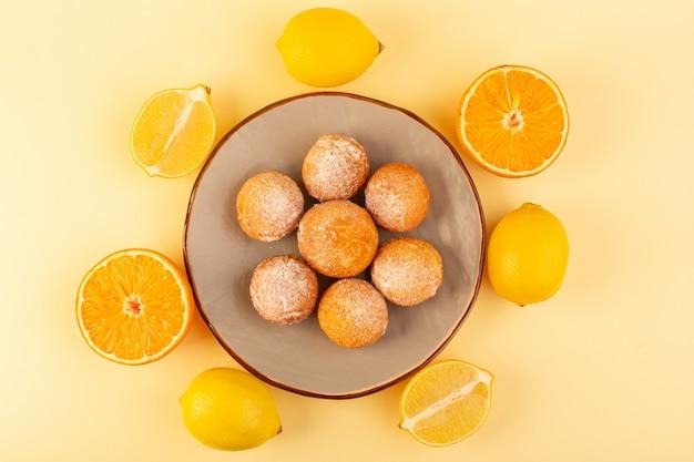 Eine draufsicht zuckerpulverkuchen rund süß gebackene köstliche kleine kuchen innerhalb runder plattform zusammen mit geschnittenen orangen auf dem cremefarbenen hintergrund bäckerei süßer keks