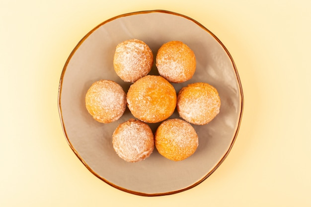 Eine draufsicht zuckerpulverkuchen runde süße gebackene köstliche kleine kuchen innerhalb runder plattform und sahnehintergrundbäckerei süßer keks
