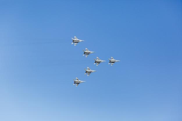 Eine dreieckige formation einer gruppe von sechs russischen militärkampfflugzeugen, die hoch in den blauen himmel fliegen