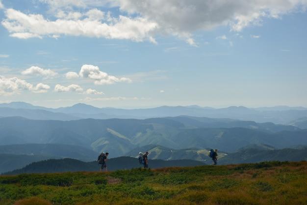 Eine dreiköpfige familie reist mit rucksäcken auf einem berg und im hintergrund himmel und berge