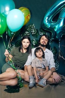 Eine dreiköpfige familie sitzt auf dem boden eines studios vor einem grünen hintergrund