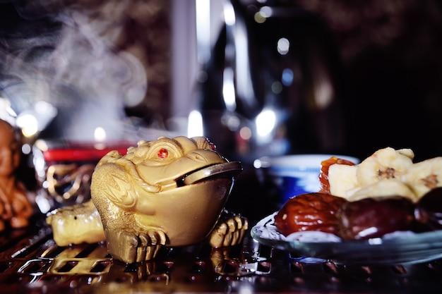 Eine dreizahnige teekröte mit einer münze im mund symbolisiert wohlstand und wohlbefinden. tee-zeremonie