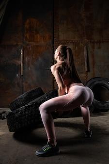 Eine dunkelhaarige trainerin in einem sportlichen rosa kurzen oberteil und gymnastikgamaschen, die sport treiben, um den knopf aufzuwärmen