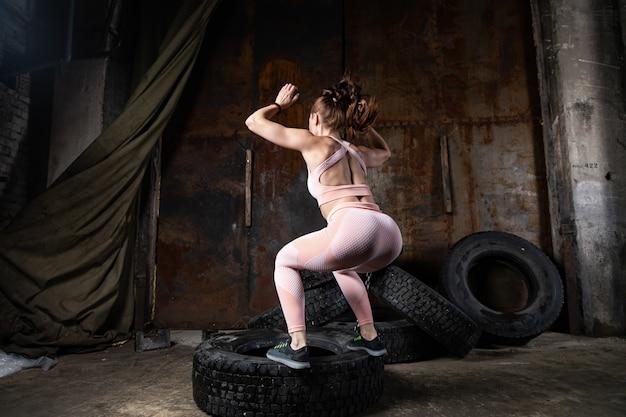 Eine dunkelhaarige trainerin in einem sportlichen rosa kurzen oberteil und gymnastikgamaschen, die sport treiben, um die knöpfe aufzuwärmen