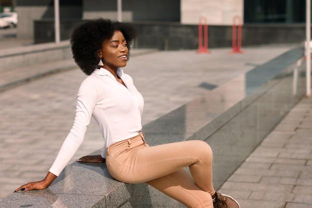 Eine dunkelhäutige afroamerikanerin sitzt in der stadt