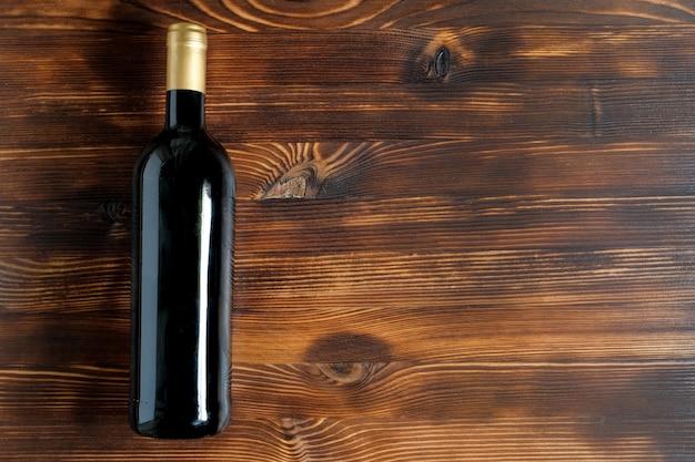 Eine dunkle flasche wein auf einem holztisch