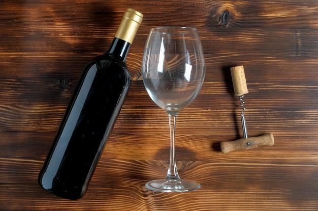 Eine dunkle flasche wein neben einem korkenzieher und einem verdrehten korken, ein glasbecher auf einem holztisch