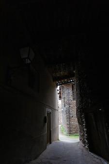 Eine dunkle gasse führt uns zu einem alten haus, das nur aus schiefersteinen und holz gebaut wurde