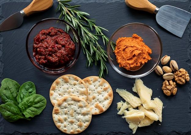 Eine dunkle käseplatte mit harissa und tomatensauce, käse, rosmarin, spinat, nüssen und keksen