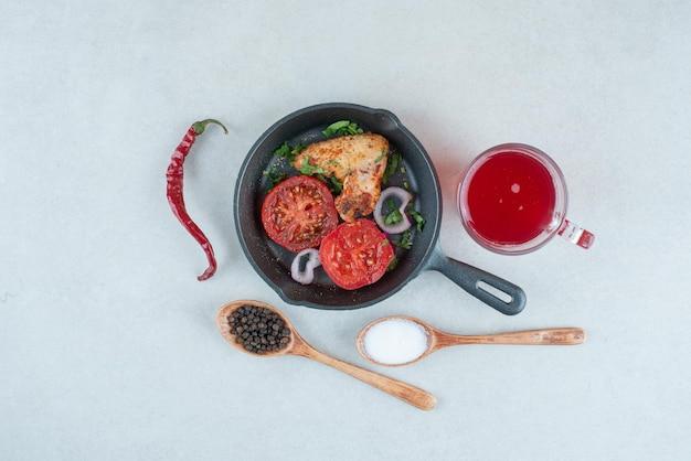 Eine dunkle pfanne mit gebratenen tomatenscheiben und hühnchen auf weißem tisch.