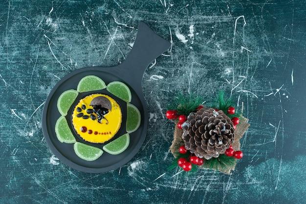 Eine dunkle pfanne mit gelbem frischem kuchen und großem weihnachtskiefernzapfen. foto in hoher qualität