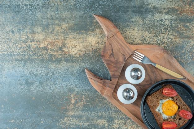 Eine dunkle pfanne mit spiegelei und schwarzbrotscheiben auf holzbrett