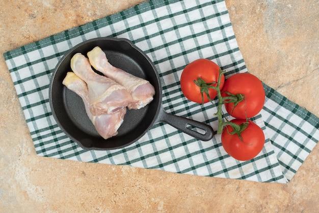 Eine dunkle pfanne mit ungekochten hähnchenschenkeln und tomaten.