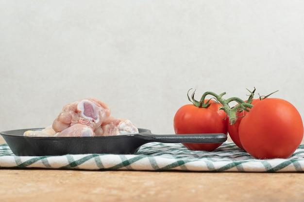 Eine dunkle pfanne mit ungekochten hähnchenschenkeln und tomaten