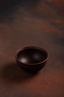 Eine dunkle tasse auf braunem tisch