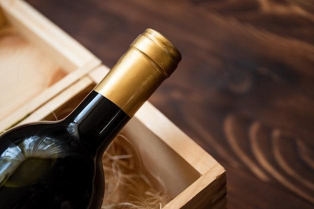 Eine dunkle teure flasche wein in einer holzkiste auf einem holztisch