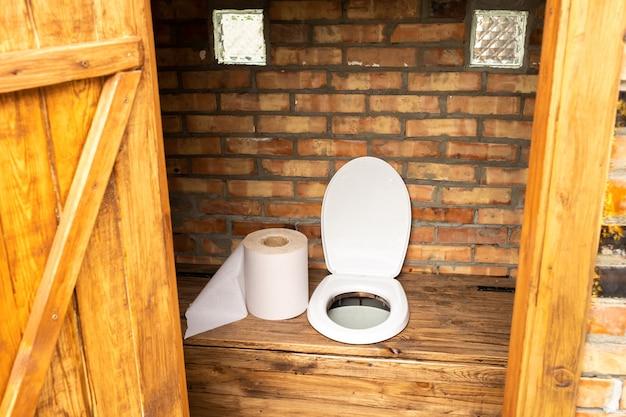 Eine einfache dorftoilette mit einer riesigen rolle toilettenpapier. große rolle toilettenpapier in der toilette.