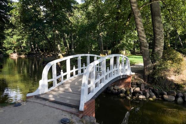 Eine einfache weiße holzbrücke, die über einen schmalen fluss gebaut wurde, um die bewegung der menschen im sommer zu erleichtern