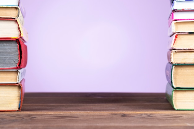 Eine einfache zusammensetzung vieler gebundenen bücher, mehrfarbiger bücher auf einem holztisch und einem rosa hintergrund.