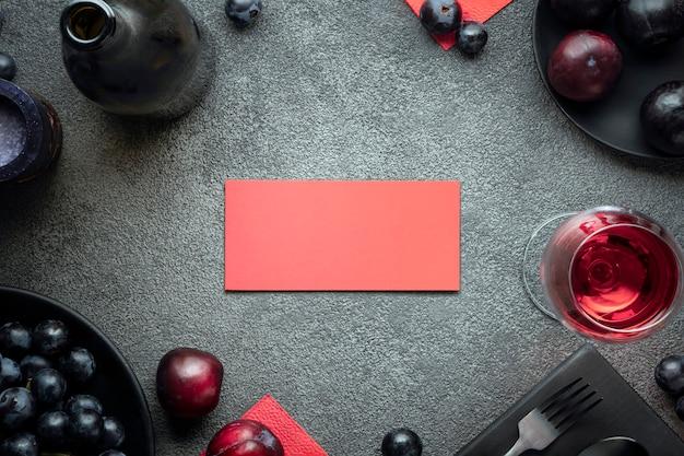 Eine einladung zum konzeptrestaurant rote visitenkarte einladungskarte umrahmt von einer flasche wein