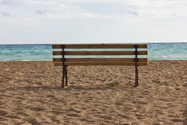 Eine einsame bank an einem leeren strand in der nähe des blauen meeres